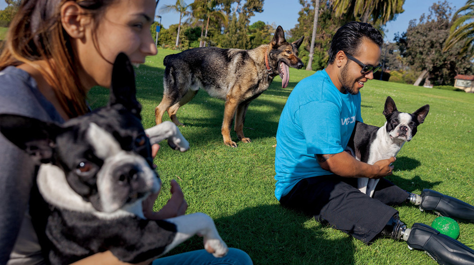 In this image from the June issue of <em>National Geographic</em>, Jose Armenta and his wife, Eliana, relax with their Boston terriers Oreo and Sassy, and Zenit, a German shepherd they adopted from the Marines. (Adam Ferguson/National Geographic )