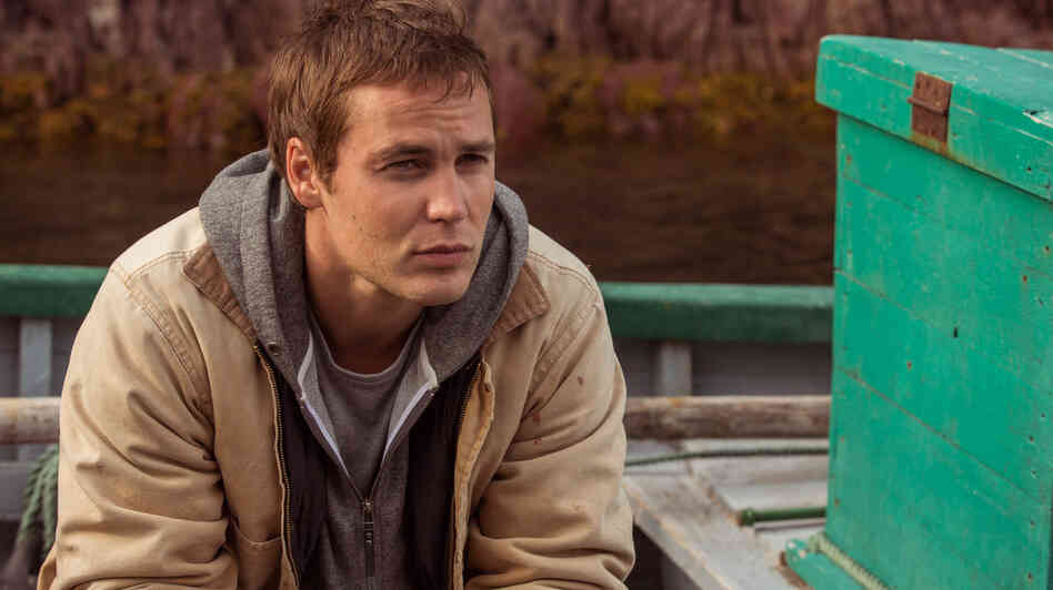 Taylor Kitsch plays Paul Lewis, a doctor in demand, in The Grand Seduction. It's a classic tale of an outsider discovering the appeal of a small town — except the rustic charm is manufactured for Lewis' benefit.