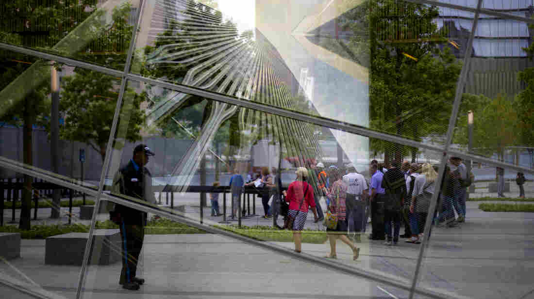 An image of the former World Trade Center haunts the reflective windows of the 9/11 Memorial Museum, now open to the public.