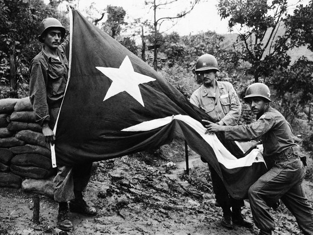 Sgt. Carmelo C. Mathews (left) holds up a Puerto Rican flag riddled by enemy shellfire, as Pfc. Angel Perales (right) points to the protruding finger of Capt. Francisco Orobitg in Korea in 1952.