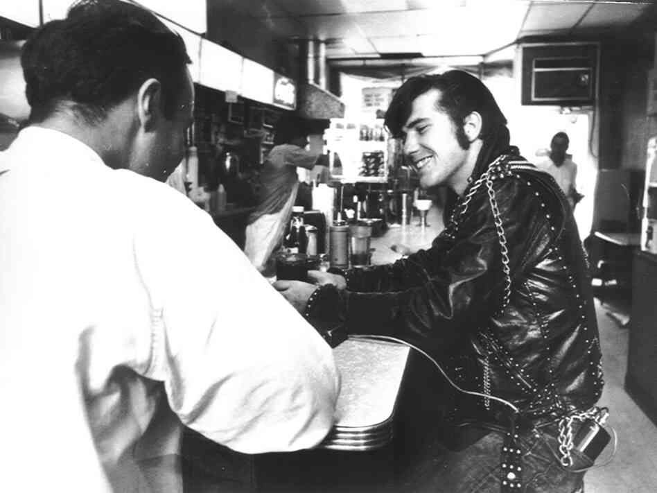 One of the first people to wear the electronic monitoring belt sits at a diner. The device can be seen in the man's back pocket with a wire leading to the other part of the device that sits on the counter.