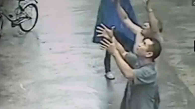 Men watch as a baby teeters on a ledge in China earlier this week. The infant fell — and was safely caught, making his rescuers into heroes in Chinese social media.