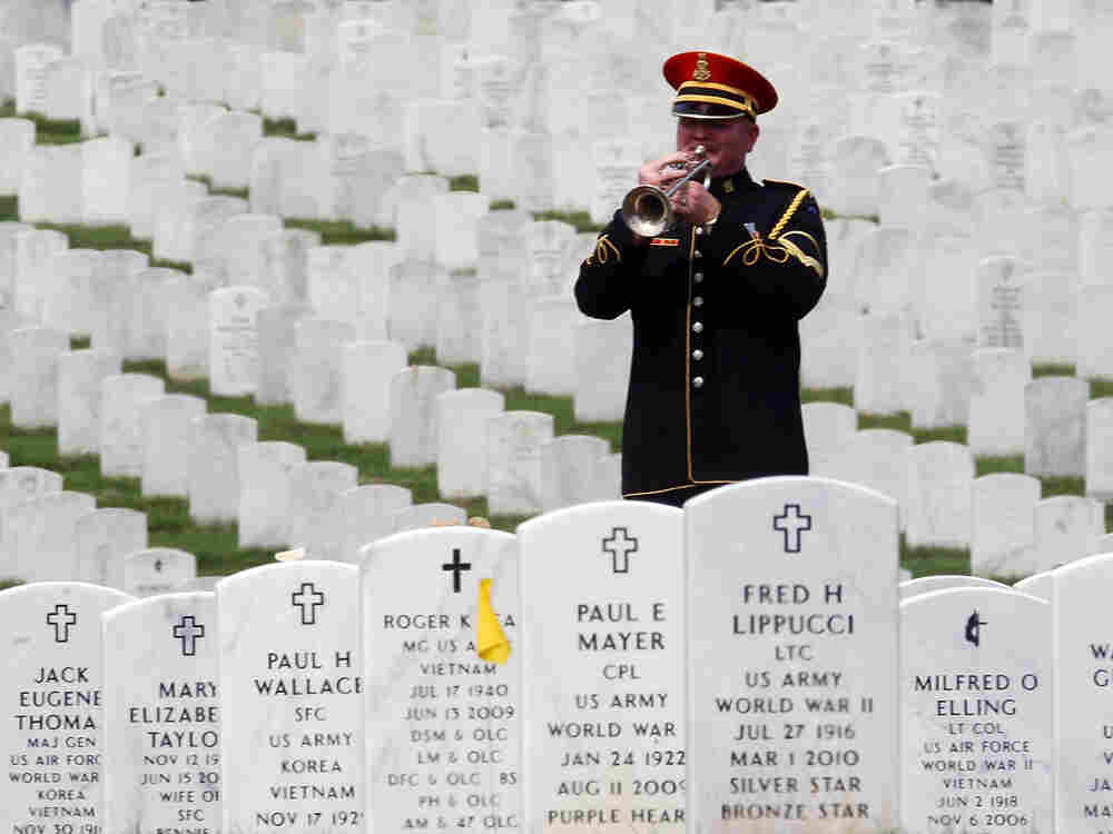 "A lone bugler plays ""Taps"" during a burial service at Arlington National Cemetery."