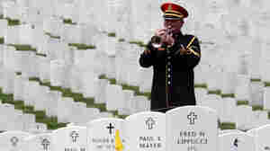 """A lone bugler plays """"Taps"""" during a burial service at Arlington National Cemetery."""