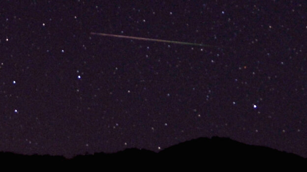 A meteor streaks across the sky north of Castaic Lake, Calif., during last year's Perseid meteor shower. NASA says that tonight's Camelopardalids shower, which has never been seen before, could rival the famous August shower.