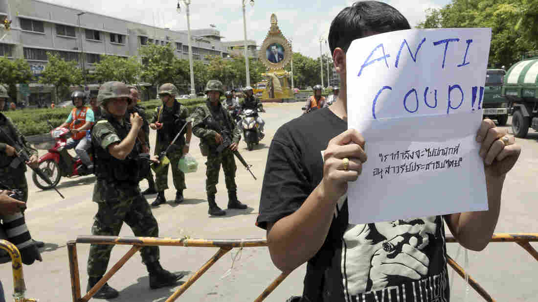 A Thai student holds an anti-coup sign in front of a group of soldiers during a brief protest near the Democracy Monument in Bangkok on Friday.