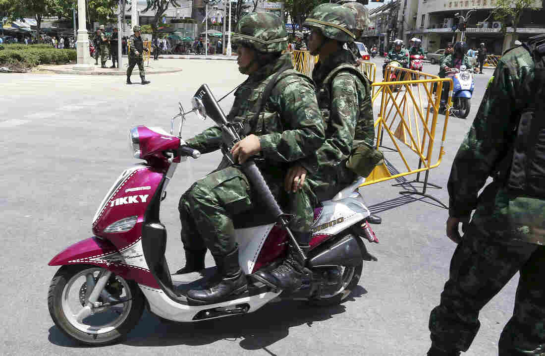 Thai soldiers patrol on a scooter Friday near the Democracy Monument in Bangkok. Thailand's ruling military summoned leaders of t