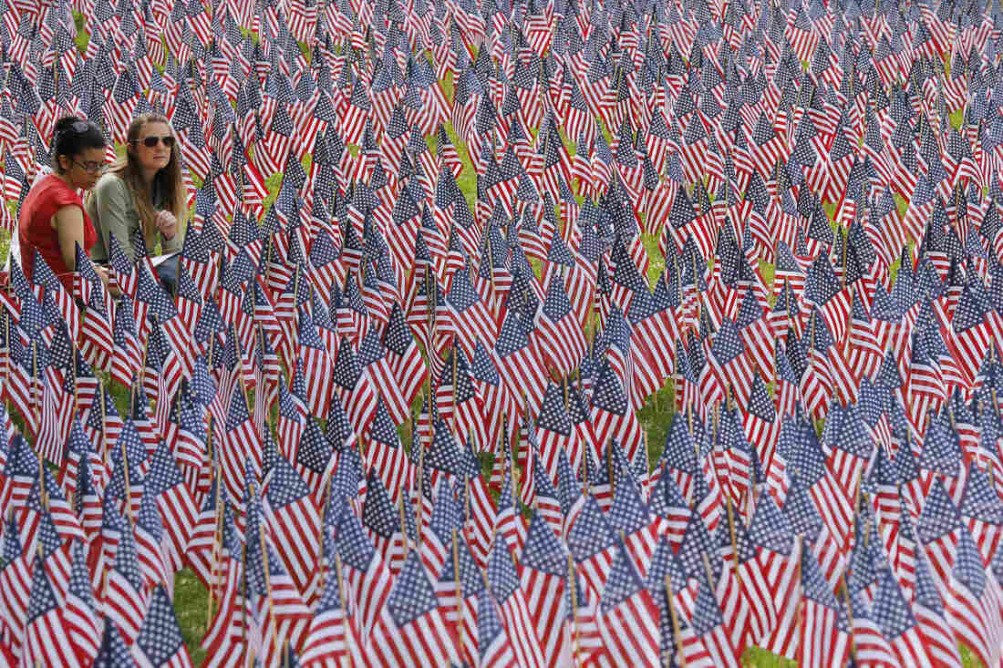 Two women sit at the edge of the field of United States flags displayed by the Massachusetts Military Heroes Fund on the Boston Common in Boston on Sunday.