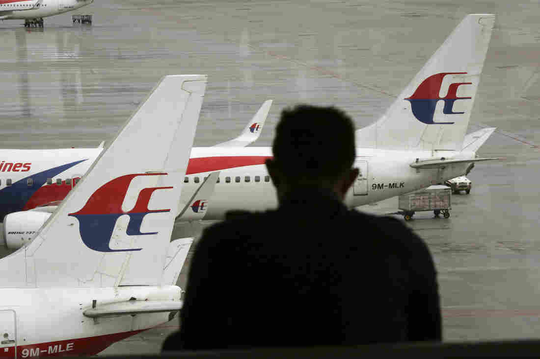 A visitor looks out from the viewing gallery as Malaysia Airlines aircraft sit on the tarmac at the Kuala Lumpur International Airport (KLIA) in Sepang, Malaysia, on May 27, 2014.