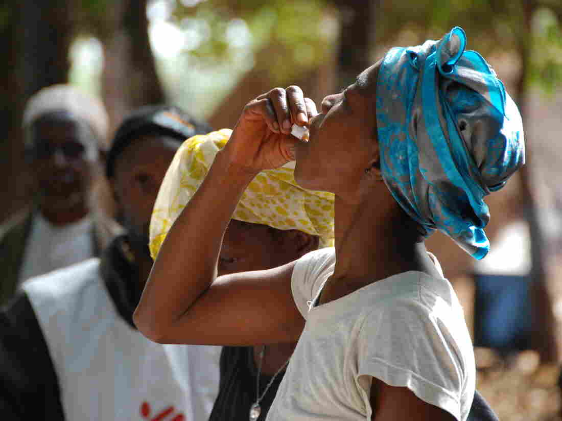 A woman in Guinea takes her first dose of the two-stage  vaccine Shanchol during the country's 2012 epidemic.