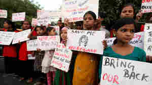 Young girls hold banners during a demonstration Thursday in Lucknow, India, after police arrested several men for allegedly raping and murdering two teenage sisters and then hanging their bodies from a tree.