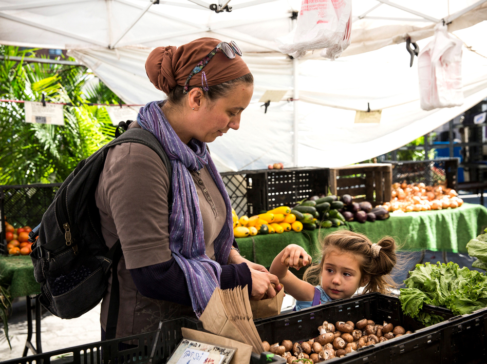 A woman and her daughter shop at a Greenmarket in New York City using Electronic Benefits Transfer, or food stamps. Government data show that fewer people were receiving the benefits in February 2014 than at the peak in December 2012. (Andrew Burton/Getty Images)