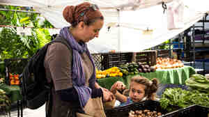A woman and her daughter shop at a Greenmarket in New York City using Electr
