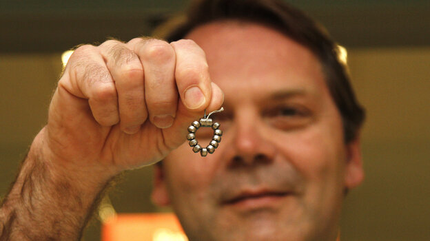Dr. Ted Trus holds a magnetic ring of beads called a LINX. It has been approved by the Food and Drug Administration for p