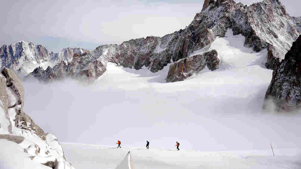 A rope of three climbers walk at 3400m on September 11, 2013 near the Dent du Géant (Giant's tooth), in the Mont Blanc massif in France and Italy.