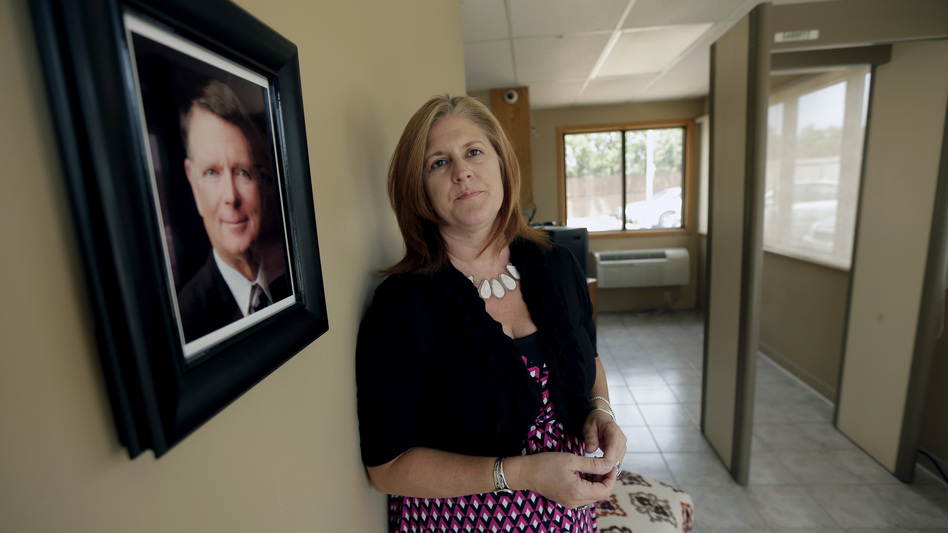 Executive Director Julie Burkhart stands next to a portrait of Dr. George Tiller at the South Wind Women's Center in Wichita, Kan. Burkhart runs the center, which recently opened in the same building where Tiller's clinic once operated. (Charlie Riedel/AP)