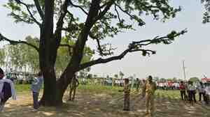 Indian police keep watch at the tree where the bodies of gang rape victims were found hanging.