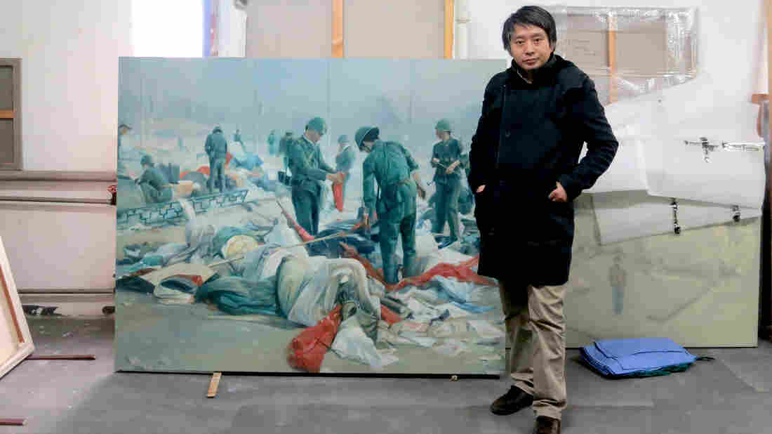 Artist and former soldier Chen Guang stands with one of his paintings last year that depicts the scene when he helped clear Tiananmen Square as a soldier.
