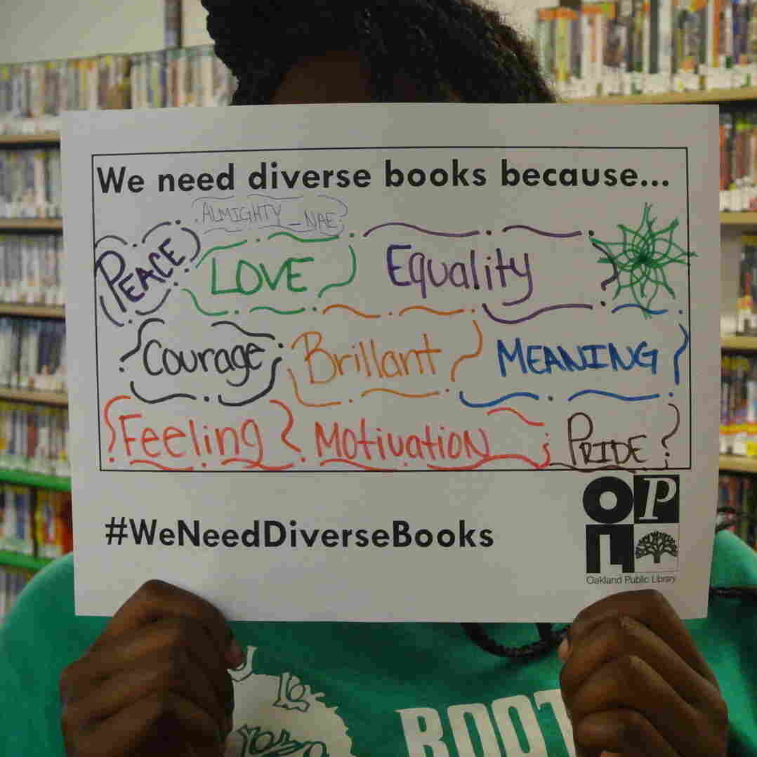 A woman holds a #WeNeedDiverseBooks sign up at the Oakland Public Library in California.