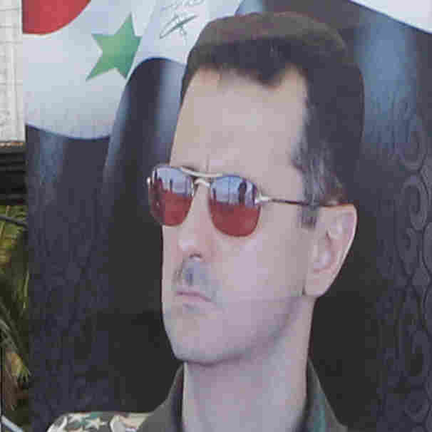 Women walk past election posters of Syria's President Bashar Assad on a Damascus street on Monday. Despite the civil war, the election will be held Tuesday in areas controlled by Assad's government. Assad became president after his father's death in 2000 and is assured of winning a third seven-year term.