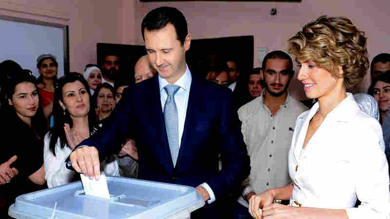 In a photo released on the Syrian Presidency's Facebook page, Syrian President Bashar Assad casts his vote on Tuesday with his wife, Asma, at his side.