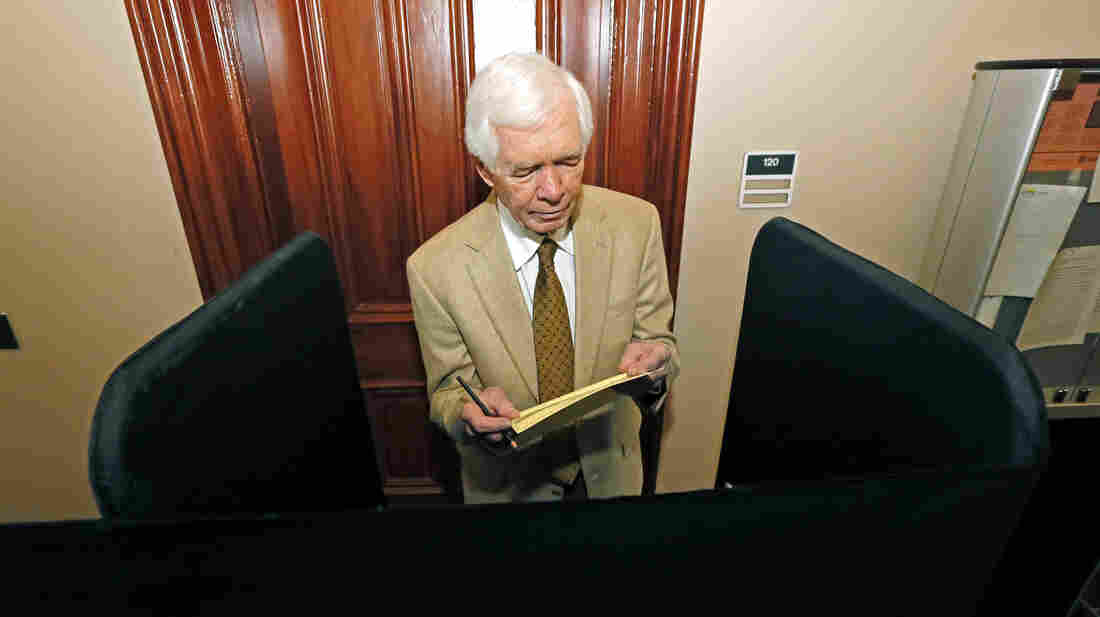 Sen. Thad Cochran, R-Miss., reads over the ballot in a privacy booth prior to voting absentee in Oxford, Miss., on Saturday.