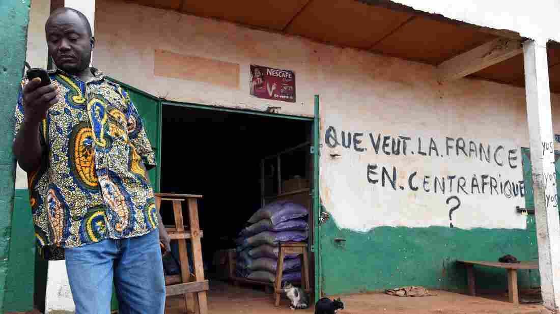A Muslim shopkeeper uses a mobile phone in front of his shop in the PK5 district of Bangui, the capital of the Central African Republic, on April 30. The nation, which struggles with conflict between Christian and Muslim militias, banned texting on Monday.