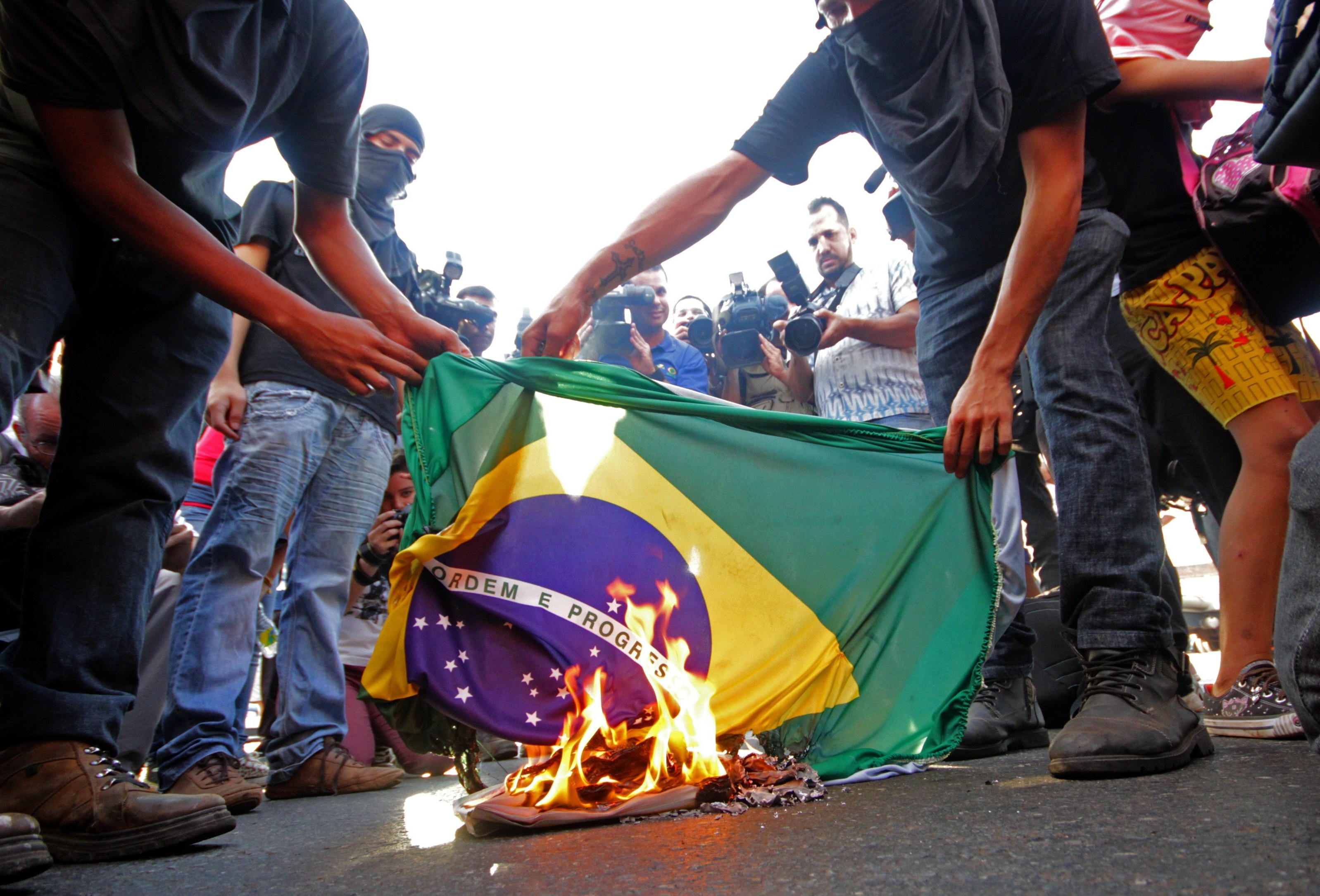 Demonstrators in Goiania, Brazil, on Tuesday burn a Brazilian flag in protest of the upcoming FIFA World Cup.
