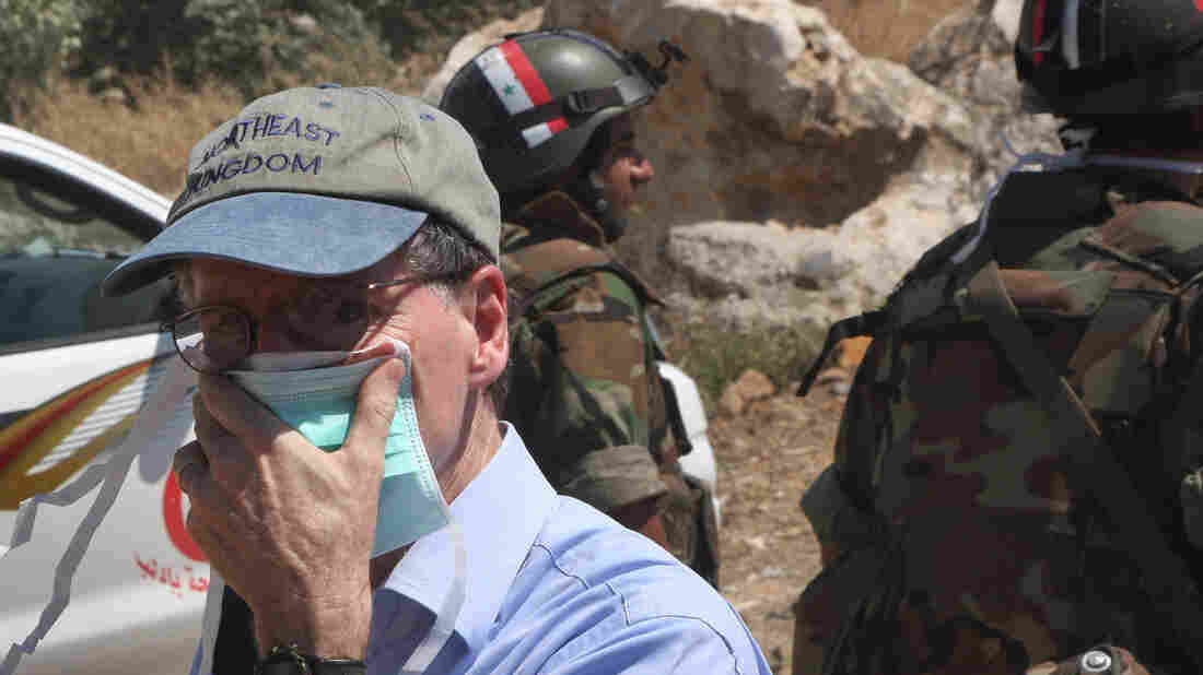 Former U.S. Ambassador to Syria Robert Ford covers his nose from the smell of dead bodies during a visit to a mass grave in the country in 2011. Ford has criticized the U.S. failure to back opposition forces early on.