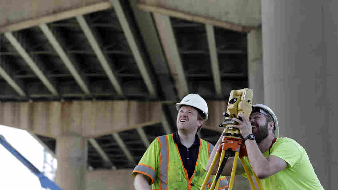 Surveyors work below the Interstate 495 bridge over the Christina River near Wilmington, Del., on Tuesday. The bridge was closed at the beginning of the week after officials discovered that eight support columns were tilting.