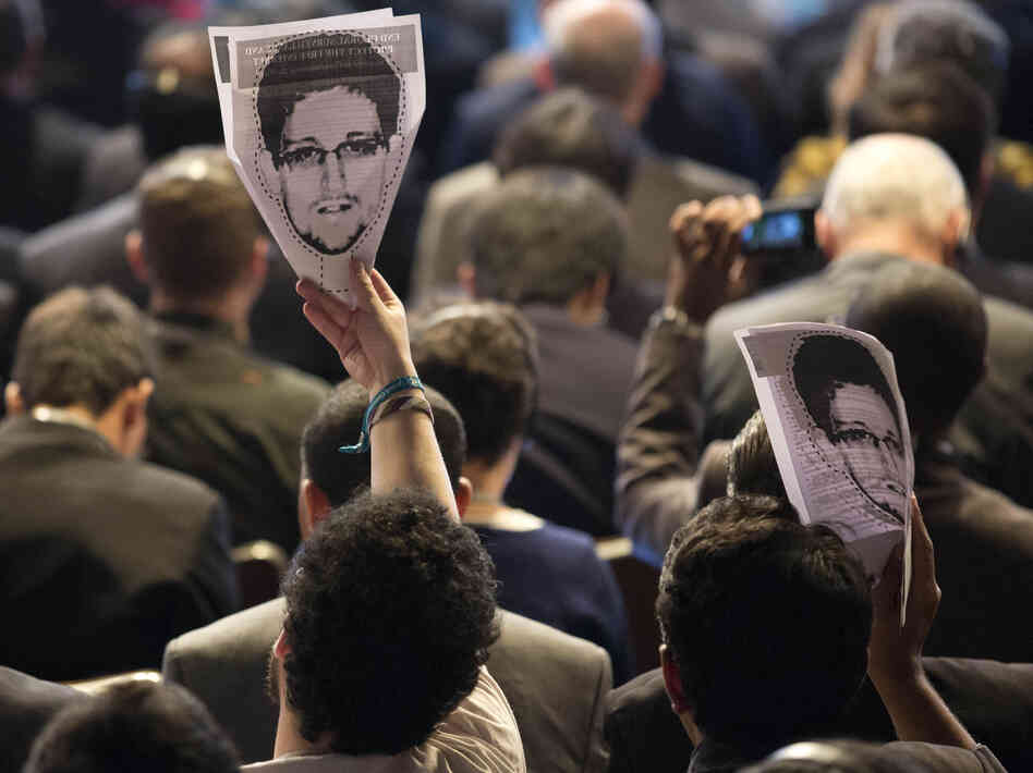 Participants hold up images of former NSA analyst Edward Snowden at an April conference on the future of Internet governance in Sao Paulo, Brazil.