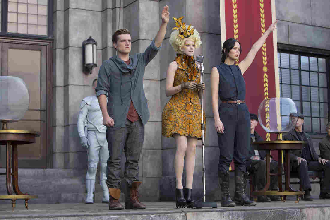 Actors Josh Hutcherson as Peeta Mellark (left), Elizabeth Banks as Effie Trinket and Jennifer Lawrence as Katniss Everdeen in a scene from the film The Hunger Games: Catching Fire. A fictional gesture from the Hollywood movie is being used as a real symbol of resistance in Thailand.