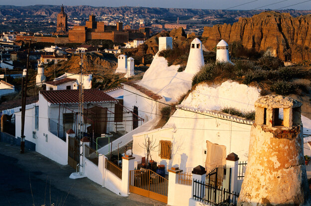Cave dwellings, inhabited for centuries, are perched on hillsides in Spain's Granada province.