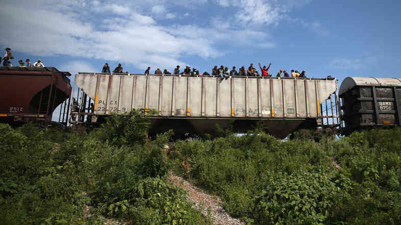 Migrants arrive at a rest stop in Ixtepec, Mexico, after a 15-hour ride atop a freight train headed north toward the U.S. border on Aug. 4. Thousands of migrants ride atop the trains, known as La Bestia, or The Beast, during their long and perilous journey through Mexico t