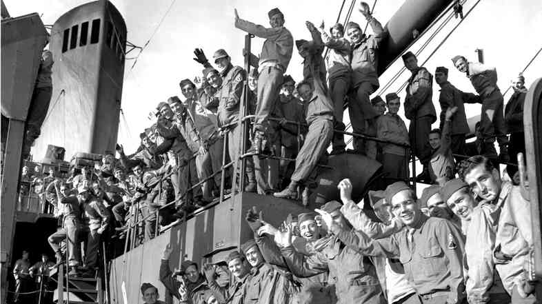 Soldiers returning from the Pacific wave from the deck of the USS General Mitchell on Dec. 11, 1945. Much of the health care demand in the VA system is from veterans of earlier wars.