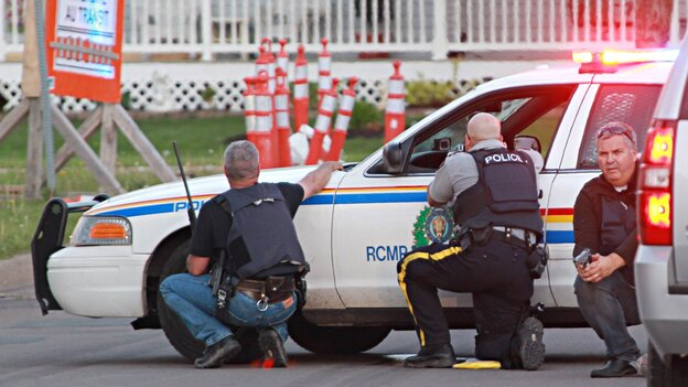 Police officers take cover behind their vehicles in Moncton, New Brunswick, on Wednesday. Three police officers were shot dead and two others were injured in a shooting Wednesday night; Canadian police are searching for the suspected