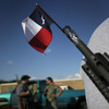 A Texas flag sticks out of the barrel of a rifle belonging to Robert Perez, as he and others with the group Open Carry Tarrant County gathered for a May 29 demonstration in Haltom City, Texas.