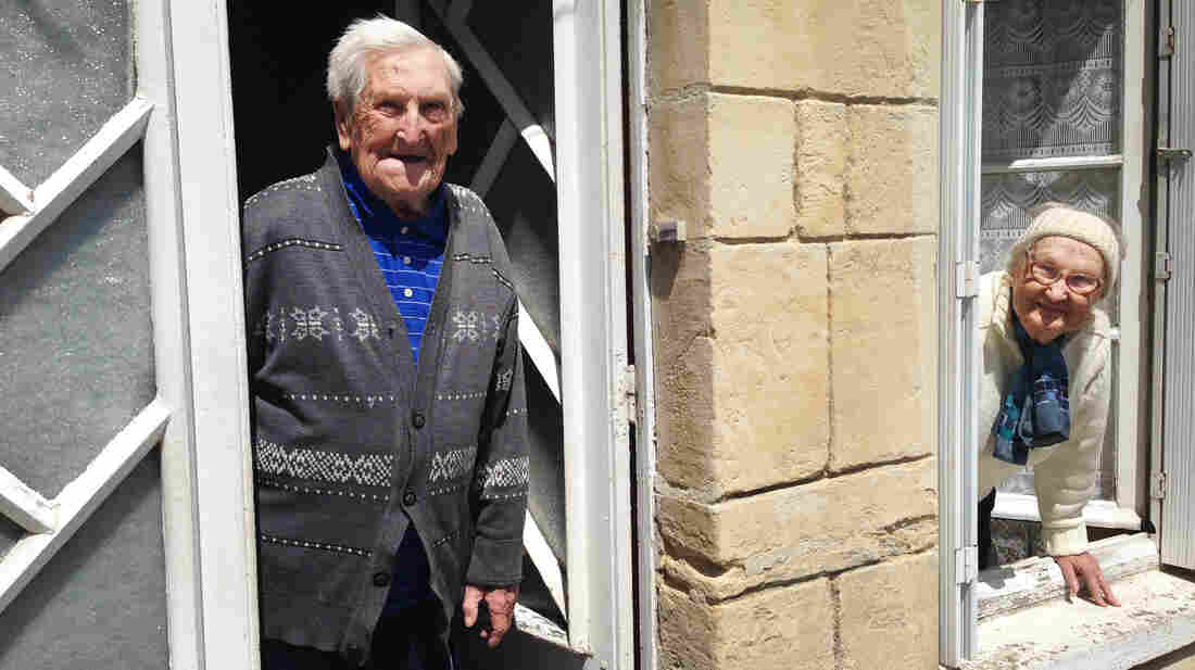 """Lucien (left) and Germaine Rigault lean out of their home in La Cambe, a tiny village in Normandy a short distance from Omaha Beach. The couple, in their 80s, were in La Cambe during the Allied landing on June 6, 1944, and live there still. """"We were scared,"""" Lucien says of that day, """"but very happy to be liberated."""""""
