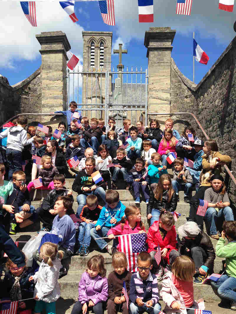 A group of children in La Cambe wave French and American flags at the unveiling of a plaque honoring the U.S. troops who liberated the village.