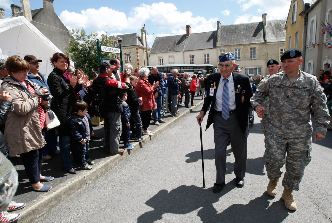 U.S. World War II veteran Arden C. Earll, 89, of Erie, Penn., landed on Omaha Beach on June 6, 1944, with the 29th Infantry Division regiment. A crowd applauds as he arrives at a ceremony in honor of the division, in La Cambe, France, as part of the commemoration of the 70th D-Day anniversary on Wednesday.