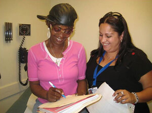 Juanita Alvarado (right), a community health worker at the Transitions Clinic in San Francisco, helps a patient.