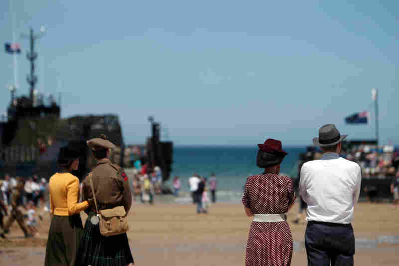 People wearing clothes in the style of the World War II era look toward the sea Friday on the beach of Arromanches, western France. Ceremonies for the 70th anniversary of D-Day included an artistic re-enactment of the coastal assault.