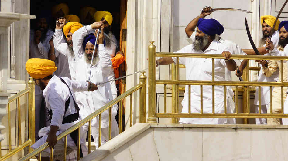 Members of a hardline Sikh group clash with guards of the Sikhs' holiest shrine, the Golden Temple, in Amritsar, India, Friday. At least 10 people were re