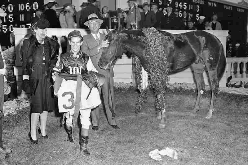 Wearing a garland of roses, Assault stands in the Kentucky Derby winner's circle in 1946, with owner Helen Kleberg (left), jockey Warren Mehrtens and owner Robert J. Kleberg, Jr.