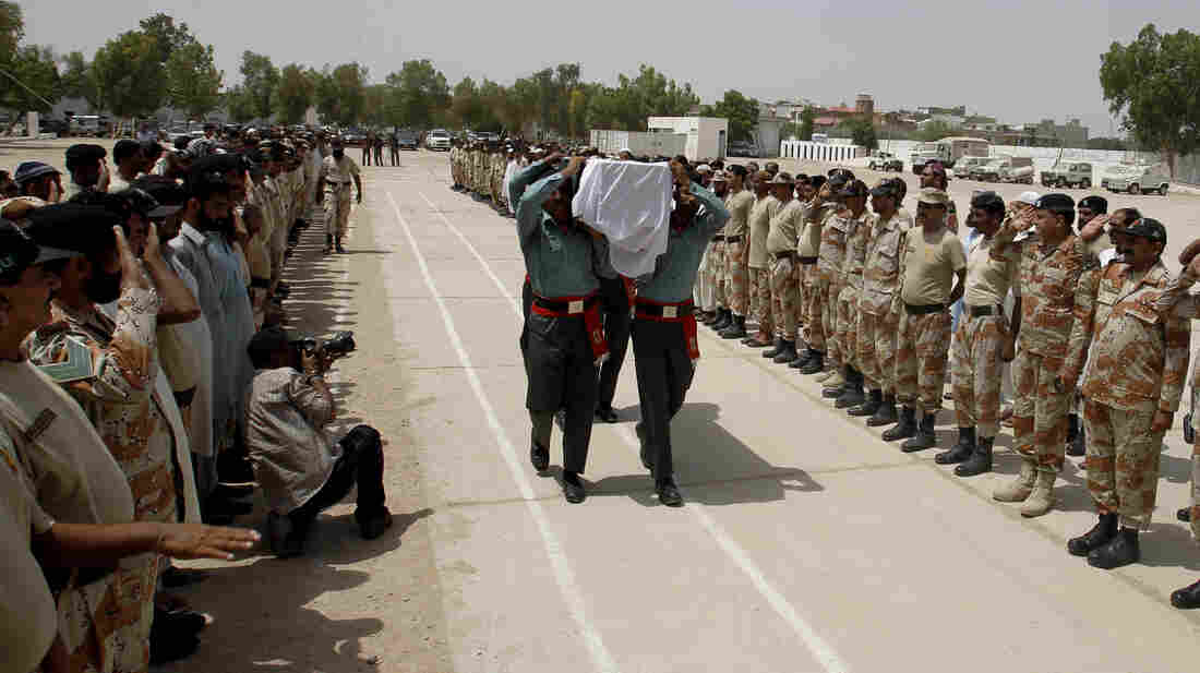 Pakistani paramilitary troops carry a coffin Monday bearing a colleague killed Sunday during a battle with members of the Pakistani Taliban who stormed the Jinnah International Airport in Karachi. More than 20 people died Sunday.