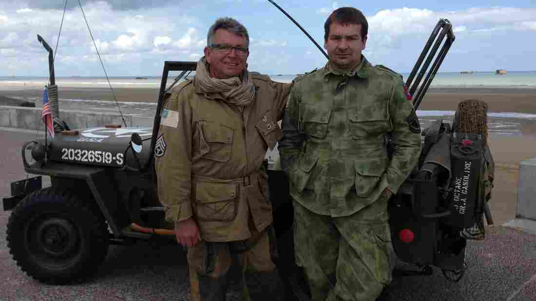 Frenchman Joseph Dellecolle, (left) 63, and his son Pierre-Yves, 40, dressed in American uniforms and drove a 1940s American military jeep to attend the D-Day commemoration on the beaches of Normandy. The elder Dellecolle says he attends every year and cries when he thinks of the many sacrifices made to liberate Europe.