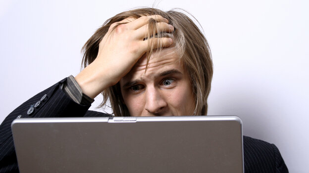 A man puts his hand to his forehead as he looks at a laptop computer screen.