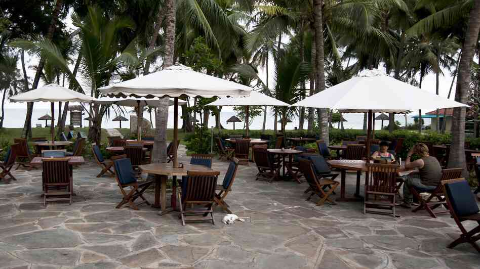 Two customers sit having a drink in the Diani Sea resort in Diani, Kenya, outside Mombasa, on May 16. Travel advisories issued by Western countries are hitting Mombasa hard, forcing hotel closures and thousands of workers to lose their jobs.