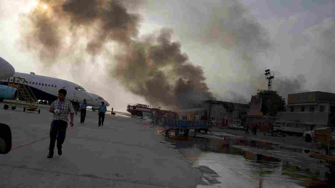 Smoke rises above Jinnah International Airport Monday morning, following a five-hour firefight between security forces and militants. The facility was open for business Monday afternoon.