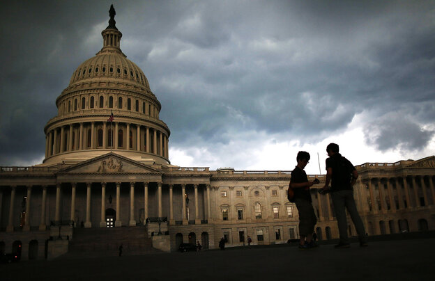 Two men stand on the plaza of the U.S. Capitol as storm clouds fill the sky June 13 in Washington, D.C.